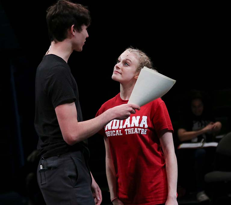 Male and female students rehearsing with scripts.