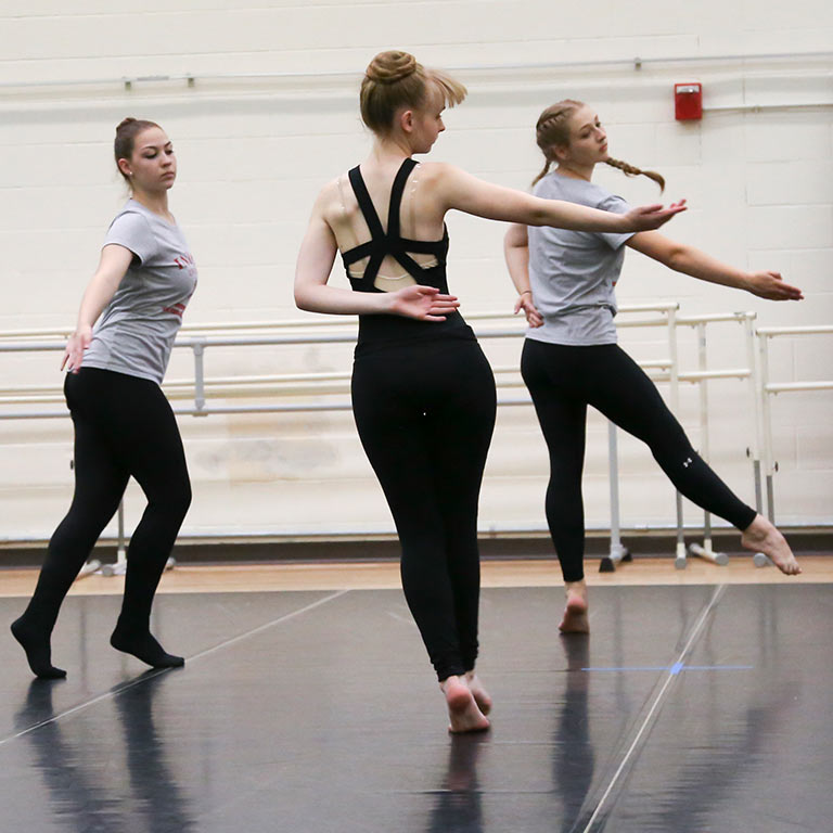 three students practicing choreography