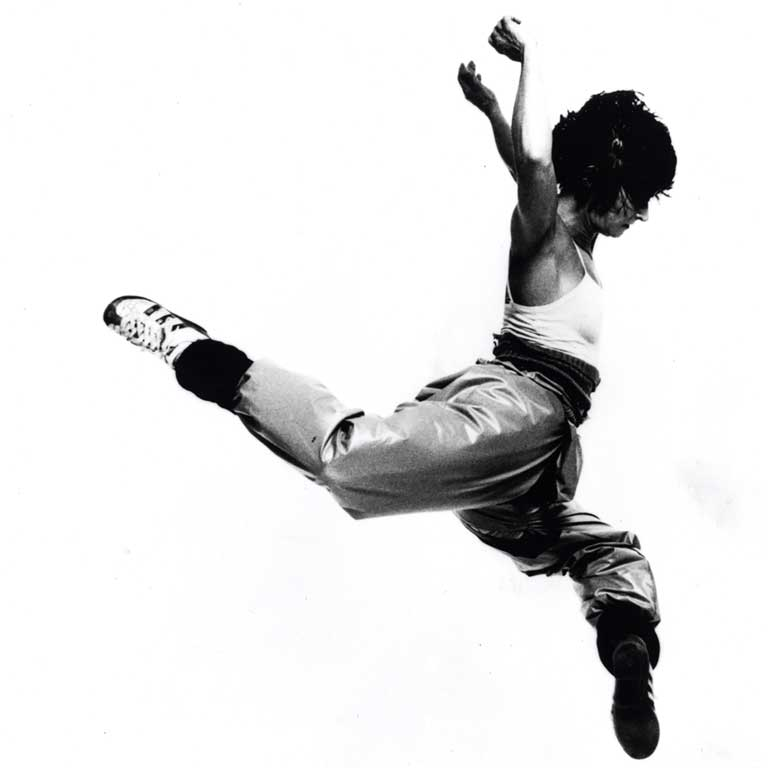 A stark black-and-white image of a dancer leaping.